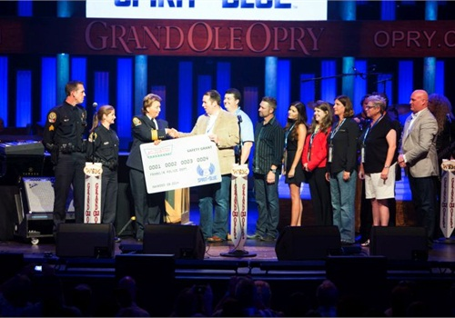 Franklin (Tenn.) PD Sgt. Brian Woodward, Officer Rachel Gober, and Chief Deb Faulkner (left to right) accepted the Spirit of Blue Safety Equipment Grant on the Grand Ole Opry stage, August 19th. The grant was presented by Spirit of Blue representatives Ryan T. Smith, Andrew Heltsley, Craig Morgan, Melissa Norrod, Kara Palm (Krispy Kreme Doughnuts), Sue Post, Diane Harbour, and Todd Parola. PHOTO: Chris Hollo for the Grand Ole Opry