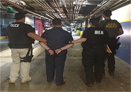 DEA agents escort an in-custody prisoner. Photo courtesy of DEA.