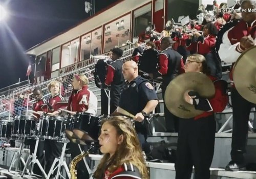 Screen grab of a video ofCorporal Les Munn of the Texarkana (AR) Police Department playing along with a high school band's drumline.