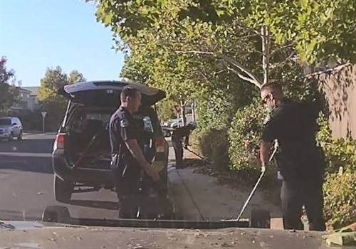 "Two officers with the Elk Grove (CA) Police Department were ""caught in the act"" of helping an 82-year-old man clear some overgrown shrubs and tree limbs from his property. Image courtesy of Elk Grove PD / Facebook."