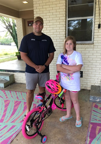 """Deputy Justin Butcher of the Garland County (AR) Sheriff's Office went """"above and beyond the call of duty"""" said Sheriff Mike McCormick in a Facebook post when he found a way to get a replacement bike for a little girl who had hers stolen. Image courtesy ofGarland CountySO / Facebook."""
