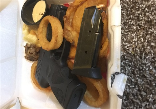 "Police officers with the Gresham Police Department found a loaded semi-automatic pistol and spare magazine in a man's ""to-go"" food order box. Image courtesy of Gresham PD / Twitter."