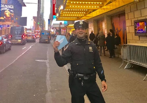 "The department said in a Facebook post, ""When a first time visitor to NYC found out she was $20 short for tickets after standing in line for 4 days, she ran for help— and luckily met Officer Dicandia. He understood the magnitude of the emergency and pulled a 20 out of his pocket so she didn't have to throw away her shot."" Image courtesy of NYPD / Facebook."