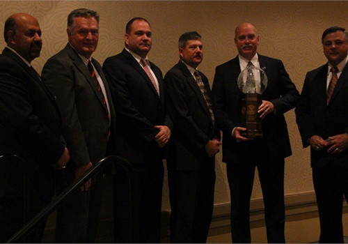 "Members of the Missouri State Highway Patrol Rural Crimes Investigative Unit stand with their award, flanked by Chief Yousry ""Yost"" Zakhary, IACP past president, left, and Dan DeSimone, senior director of Integrated Solutions & Business Development for Thomson Reuters."