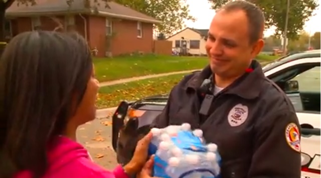 Urbandale, IA, woman gives bottled water to an Urbandale officer. Both the officer and the woman teared up as they talked. (Photo: KCCI TV screen shot)