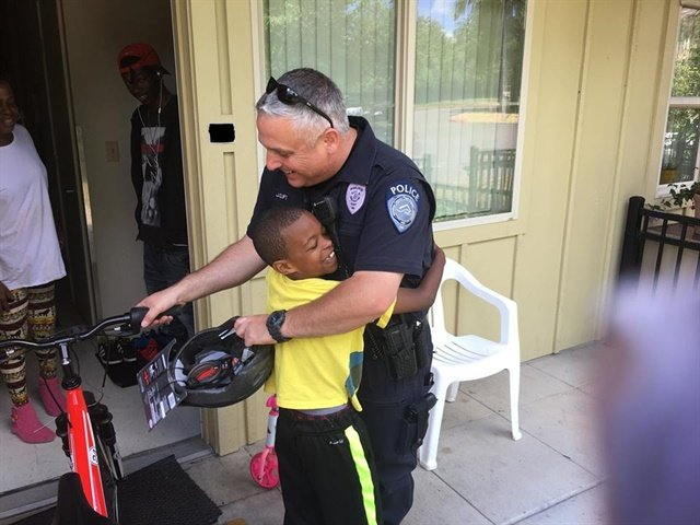 Officer Clift of the Kent (WA) Police Department gets a hug from a boy after gifting the child a bicycle. (Photo: Kent PD/Facebook)