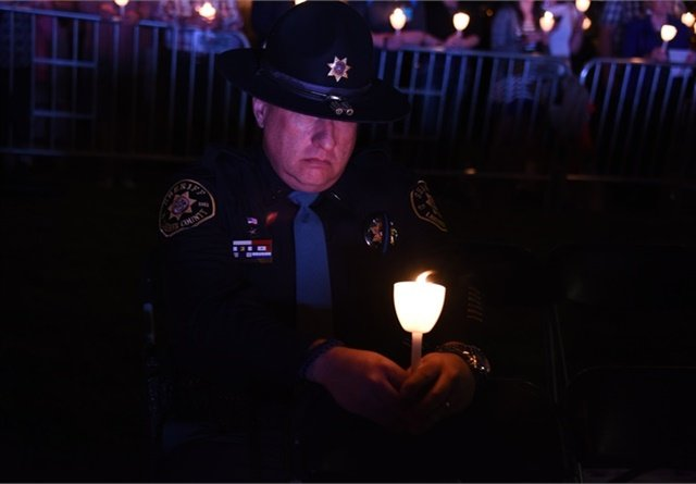 Officer honors the fallen at annual Candlelight Vigil at the National Law Enforcement Officers Memorial in Washington, DC. (Photo:  Lynn Cronquist)