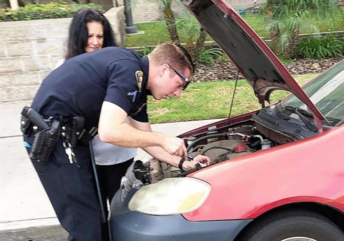 An officer with the Long Beach (CA) Police Department was captured in an image making the rounds on social media installing a replacement car battery after a woman reported her original battery stolen. Image courtesy of LBPD / Facebook.