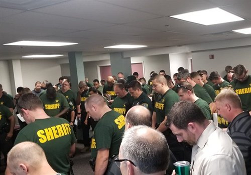 The Leon County (FL) Sheriff's Office posted a picture to Facebook showing deputies bowing their heads in prayer as they braced for the imminent landfall of Hurricane Michael on October 9, 2018. Image courtesy of Leon County SO / Facebook.