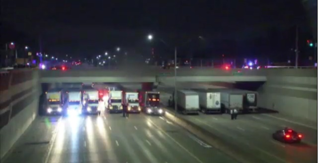 Michigan State Police used a collection of tractor-trailers trucks to prevent a man from jumping off of a freeway overpass early Tuesday. (Photo: Fox2 Detroit Screen Shot)