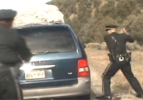 Officer Elias Montoya (foreground) prepares to fire upon the minivan as it drives away from officers. (Photo: Still from New Mexico State Police Video)