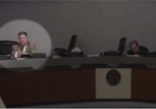 After yelling for his fellow councilmen to get down, former officer John Elder drew his handgun and prepared to respond if the shooter came in the council hall, (Photo: Screen Grab of video)