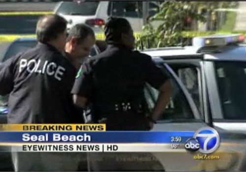 Seal Beach (Calif.) Police officers load the mass-shooting suspect into a squad car. Screenshot: ABC News.