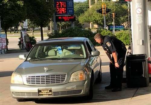 Seth Kazz—who owns and operates the Little Mack Citgo in St. Clair Shores, MI—posted a picture on Facebook of Officer Todd Bing talking with Delores Marotta, whose husband had recently passed away, and who had only three dollars for available for gasoline. Image courtesy of Seth Kazz / Facebook.