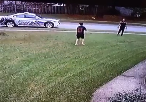 A 10-year-old boy was tossing a football to himself when an officer with the Summerville (SC) Police Department stopped his patrol vehicle and asked him if he had anyone to play with. Image courtesy of Summerville PD / Facebook.