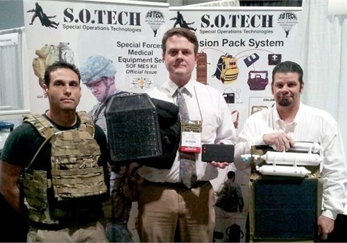 (From l. to r.) S.O. Tech's Lead Sales Rep Neil Trusso, CEO Jim Cragg, and DynGlobal's Solar Engineer Rob Hill. Cragg is holding the vest-mounted solar panel and a battery. Hill is holding a representation of a solar-power and water filtration system. Photo: S.O. Tech