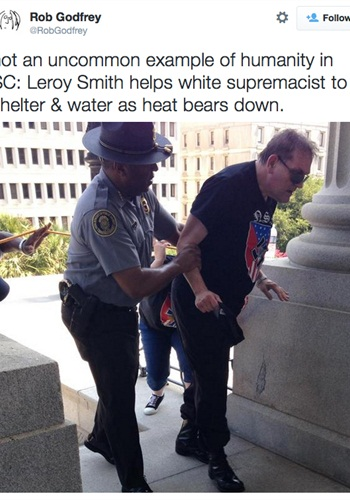Leroy Smith, director of the South Carolina Department of Public Safety, comes to the aid of a heat-stricken man wearing a swastika T-shirt at a weekend Klan rally in Columbia. (Photo: Rob Godfrey via Twitter)