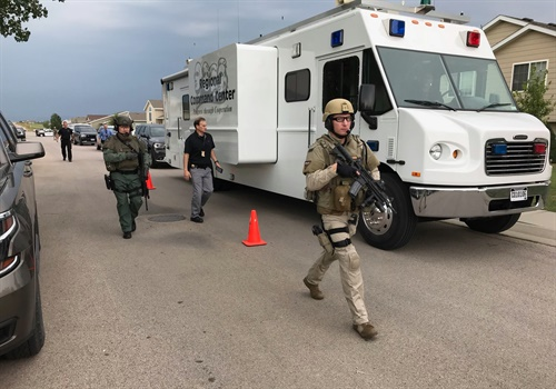 Officers rush to arrest a man who reportedly opened fire on officers and briefly held two people hostage. Image courtesy ofPennington County Sheriff's Office / Facebook.