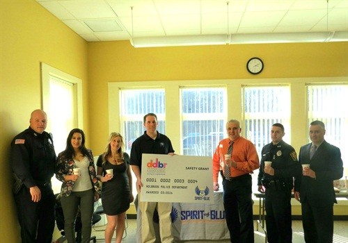 Chief William Smith (center right) accepted the Spirit of Blue safety grant on behalf of the officers of the Holbrook Police Department, along with Town Administrator Timothy Gordon (far right). Presenting the grant was Spirit of Blue Executive Director, Ryan T. Smith (center left), and local Dunkin' Donuts franchise owners Monica MacFarlane and Nicole Loredo.