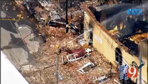 Firefighter sprays down the ruins of a home in Talihina, OK. The home burned after a booby trap exploded while law enforcement tried to serve a warrant to the resident. Four officers were injured in the explosion; the gunman was killed in a shootout with offficers. (Photo: News9 Screen Shot)