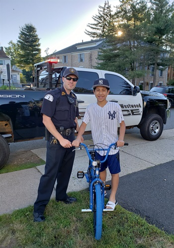 "Officer Ryan Sestanovich and ""Q,"" the 13-year-old boy who Sestanovich helped to replace his stolen bike. (Photo courtesy of Westwood PD / Facebook)"