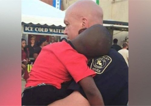 Officer David Taylor holds a lost child at last weekend's International Rice Festival in Crowley, LA. The boy was quickly reunited with his mother. (Photo: Facebook)