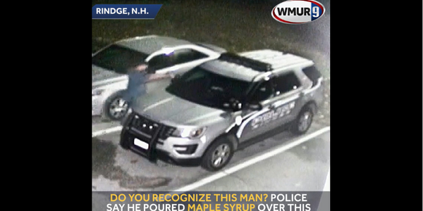 Screen grab of a video of aRindge (NH) Police Department squad carbeing vandalized by a man...