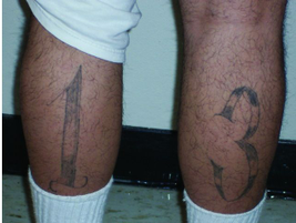 A Sureño tattoo on both calfs displays the use of the number 13.