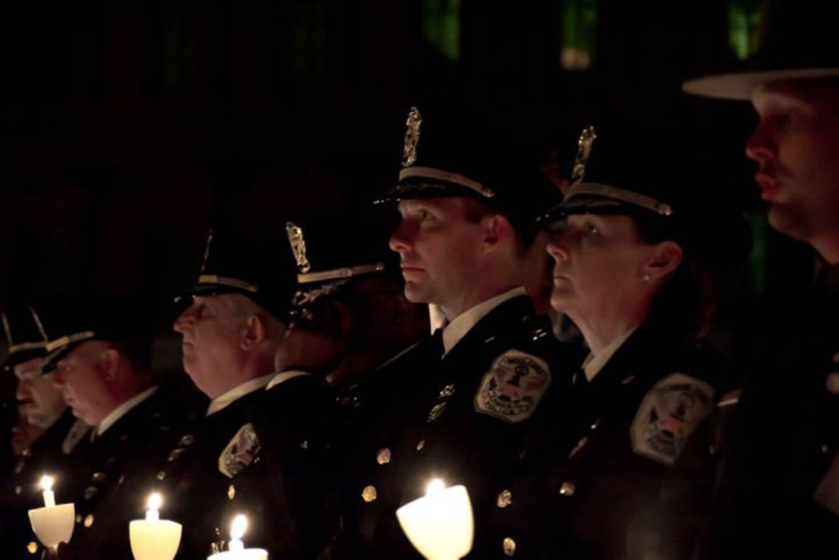Officers with the U.S. Park Police hold their lighted candles during the NLEOMF's annual...