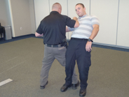 To bring the suspect to the ground, step through and start the leg sweep. Bring your right elbow...