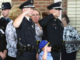 Officers and a young boy salute Officer Ellis.