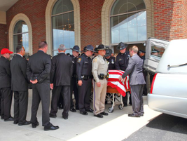 Officers prepare to load Officer Ellis into the hearse.