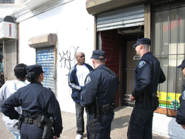 Officers talk with the patron of a convenience store in Camden, where drug activity and...