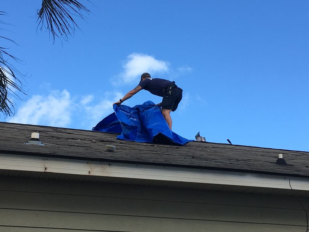 Miami officer places tarp on hurricane-damaged roof. (Photo: Courtesy of Javier Ortiz)