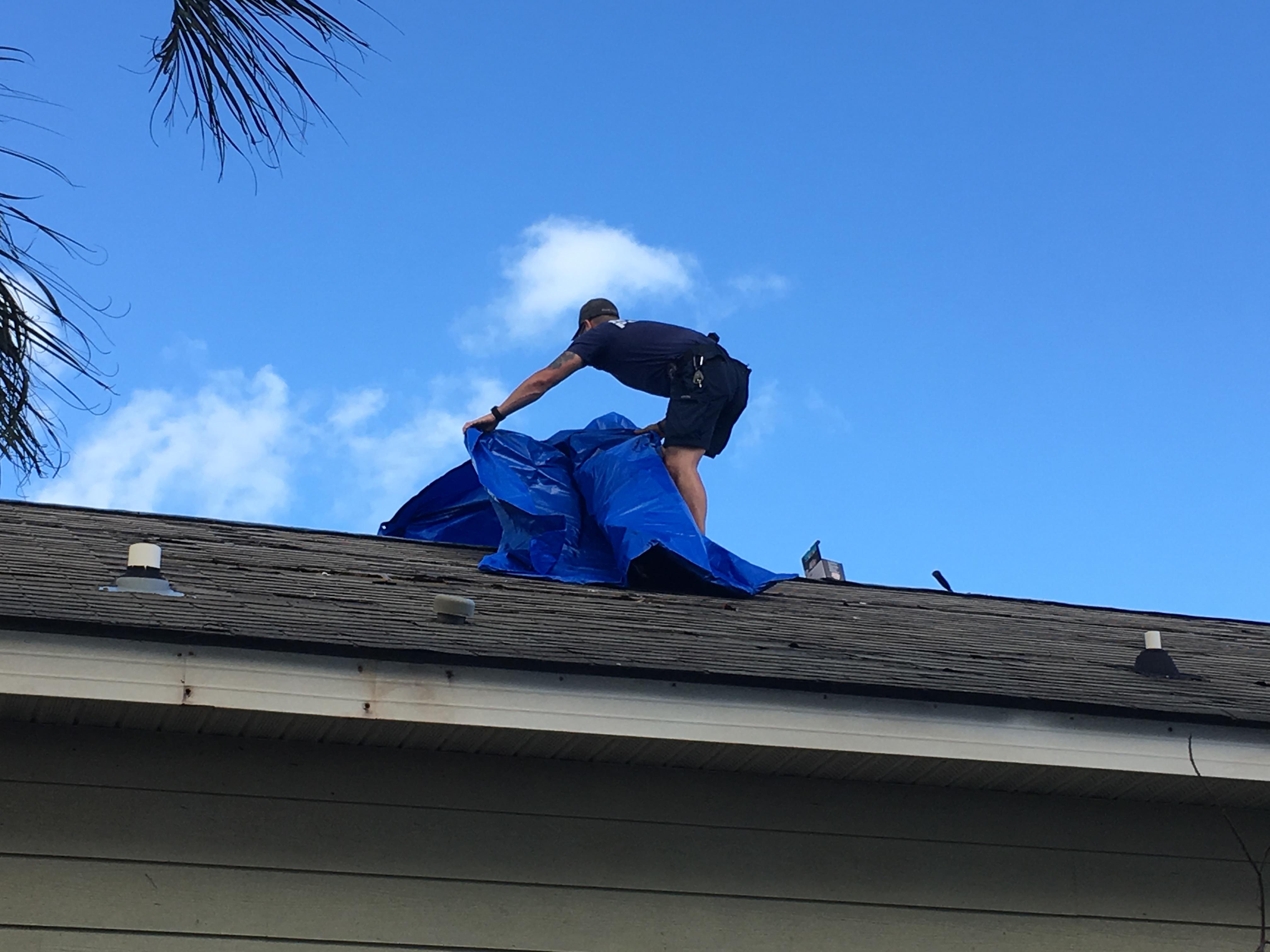 Miami officer places tarp on hurricane-damaged roof. (Photo: Courtesy of Javier Ortiz)