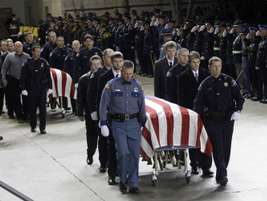 Officers and family members escort the four caskets of the slain Lakewood police officers into...