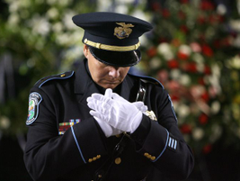 A color guard maintains a folded-hands position near the caskets of the four slain Lakewood...