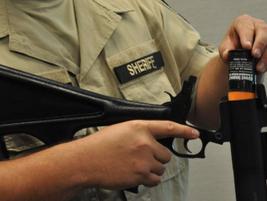 A sheriff's deputy loads a single-shot 40 mm round into a launcher.