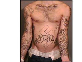 A Nazi white supremacist gang member wears tattoos of a swastika symbol and picture of Adolph...
