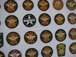 Many sheriff's agencies in Georgia opt for the uniformity of a round patch with a star and...