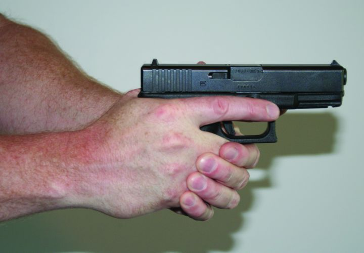 To get a two-hand grip, bring your off hand up to the other side of the gun and place the meaty...