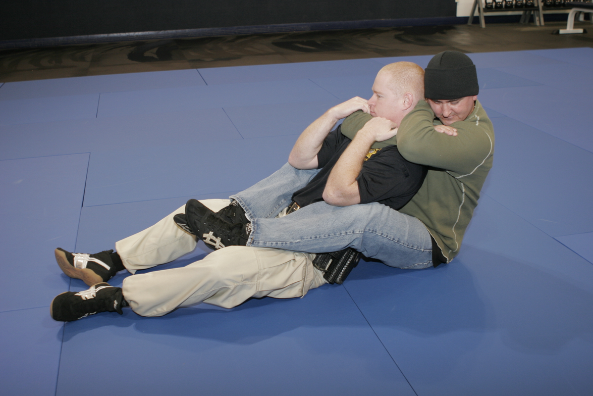Photos 1-5 show an escape from the rear naked choke. Use both of your hands to pull downward on...
