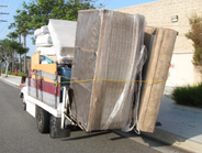 An overloaded truck can barely carry mattresses and a sofa.