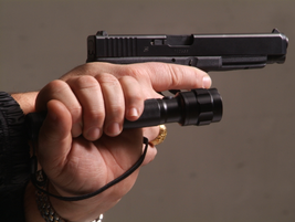 Harries—Hold the handgun at a low-ready position. With your non-gun hand, grip the flashlight in...