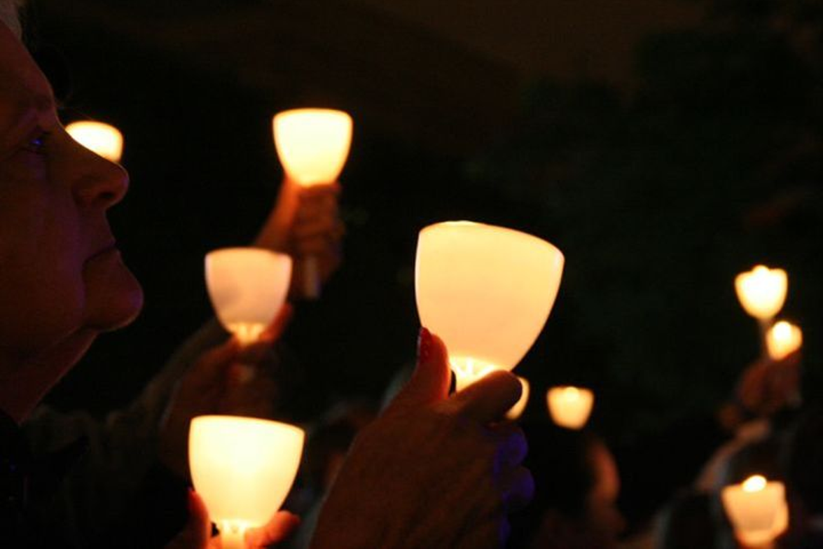 Officers and survivor families hold their candles during the 2010 National Law Enforcement...