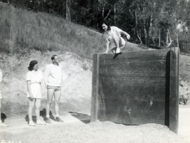 Police women scale a wall during training at the Los Angeles Police Academy's obstacle course in...