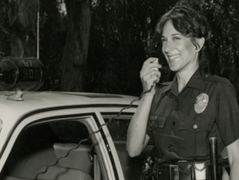 A female police officer working patrol in the 1980s uses her two-way radio. Photo courtesy of...