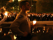 A lone law enforcement officer holds a candle during the vigil. Photo courtesy of NLEOMF.